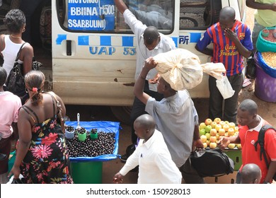 KAMPALA, UGANDA - SEPTEMBER 28, 2012.  A line of passengers enter into a mini-bus while passing different types of food for sale in the main taxi park in Kampala, Uganda on September 28,2012.