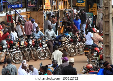 KAMPALA, UGANDA - SEPTEMBER 28, 2012.  Motorcycle taxis and drivers wait on the streets for passengers as people walk by in Kampala, Uganda on September 28,2012.