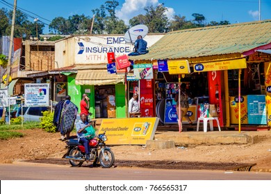 KAMPALA, UGANDA – SEPTEMBER 28, 2017: Typical street picture of a Kampala street in Uganda. Mini bus, boda boda, shops and construction all in one shot.