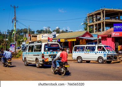 KAMPALA, UGANDA – SEPTEMBER 28, 2017: Typical street picture of a Kampala street in Uganda. Mini bus, boda boda, shops and construction all in one shot.