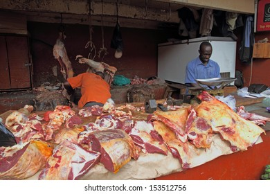 KAMPALA, UGANDA - SEPTEMBER 29 2012.  Two African men work and prepare meat in a dirty open air market in Kampala, Uganda on September 28,2012.