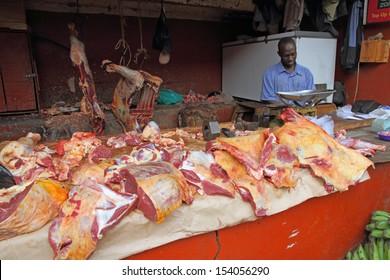 KAMPALA, UGANDA - SEPTEMBER 29, 2012. An African butcher works in his butcher shop in the food market of Kampala, Uganda on September 28,2012.