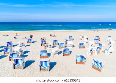 KAMPEN BEACH, SYLT ISLAND - SEP 10, 2016: people sunbathing and wicker chairs on sandy beach in Kampen village, Sylt island, Germany.