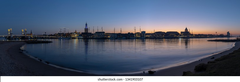 Kampen, Netherlands - February 27, 2019: Panorama of the monumental city of Kampen at the river IJssel with some tall sailing ships and the church during sunset.