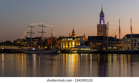 Kampen, Netherlands - February 27, 2019: Monumental city of Kampen at the river IJssel with some tall sailing ships and the church tower during sunset.