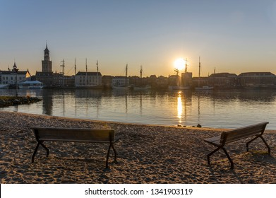 Kampen, Netherlands - February 27, 2019: The monumental city of Kampen at the river IJssel with some tall sailing ships and the church. In front two benches on the beach.
