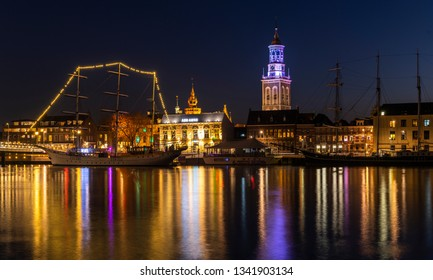 Kampen, Netherlands - February 27, 2019: Monumental city of Kampen at the river IJssel with some tall sailing ships and the church tower during night.