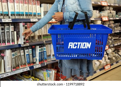 KAMPEN, THE NETHERLANDS - JULY 12, 2016: Shopping woman with shopping basket in a Action discount superstore. Action is a Dutch discount store-chain. Sells in their stores low budget products.