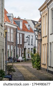 Kampen, The Netherlands, July 26, 2020: narrow curving street in the old town with traditional brick and plaster houses