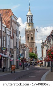 """Kampen, The Netherlands, July 26, 2020: view along Oudestraat, the main shopping street with the leaning """"New Tower"""" in the background"""
