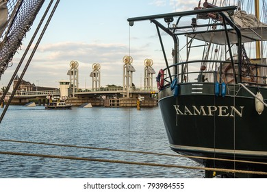 KAMPEN, NETHERLANDS - JUNE 5, 2017: Summer evening at IJssel river in Kampen. A yacht sails towards the city bridge, which can be seen in the background. In the foreground two sailing ships.