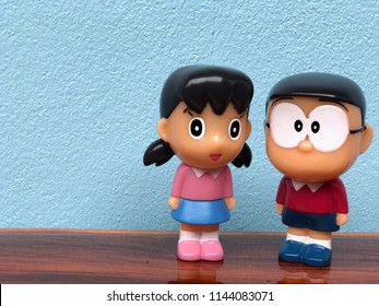 Kamphaeng Phet, THAILAND - JULY 28, 2018: Shizuka Minamoto and Nobita Nobi figure model are standing together on the wooden table, isolated in blue concrete wall background. Doraemon cartoon concept.