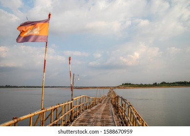 KAMPONG CHAM, CAMBODIA, APR 23, 2019: cambodian flag on old traditional bamboo wooden bridge across Mekong river (from Koh Paen island to Kampong Cham), Cambodia