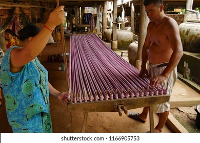 Kampong Cham, Cambodia. Nov 9th 2016. Hand weaving cloth in rural Cambodia. Preparing to remove the 6 meter warp from the warping board or cradle.