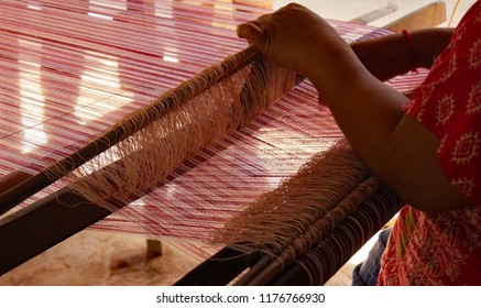 Kampong Cham, Cambodia. Oct 4th 2016. In a rural Cambodian home, a woman undertakes the painstaking task of preparing the warp for weaving on the loom.