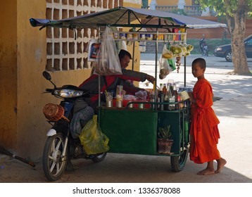 Kampong Thom, Cambodia. 19-12-2018. Outside the walls of Wat Kampong Thom a child monk buys a meal form a food vendor.