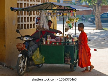 Kampong Thom, Cambodia. 19-12-2018. Outside the walls of old Wat Kampong Thom a child monk buys a snack form a food vendor.
