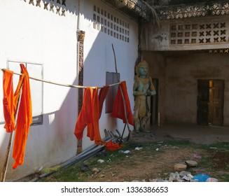 Kampong Thom, Cambodia. 19-12-2018. Saffron robes and a statue within the old walled temple of Entri Sam Voreak Pagoda, also known as the old Wat Kampong Thom Temple.