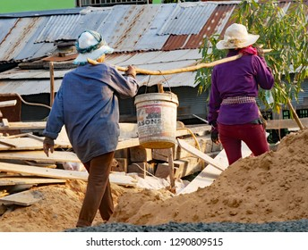 Kampong Thom, Cambodia. 20-12-2018. Women working on a building site carry rocks in the construction of a house.