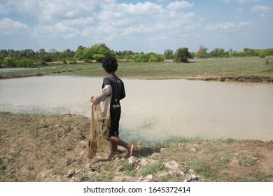 Kampong Thom, Cambodia-January 25, 2020: A man casting a net along National Highway 219 near Sambor Prei Kuk in Kampong Thom, Cambodia