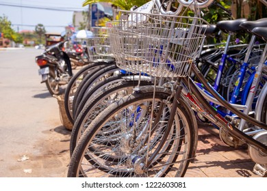 Kampot, Cambodia - 12 April 2018: city bicycles for rent closeup, with street on background
