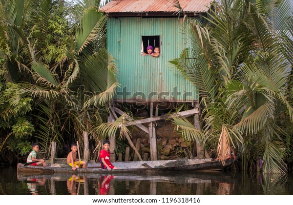 Kampot, Cambodia - Dec 10 2013 : Wooden green house on stilts on the banks of Tonle Sap river with boat passing by carrying three boys