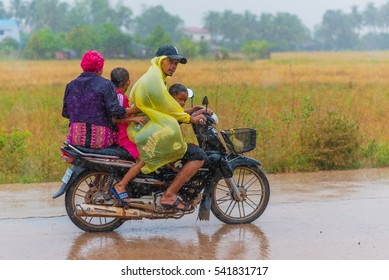 KAMPOT, CAMBODIA - DECEMBER 14: Cambodian family (unidentified) rides a scooter foursome (two adults, two children) while getting wet in heavy rain on December 14, 2016 in Kampot, Cambodia.