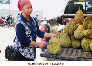 Kampot, Cambodia - May 16th, 2019: Cambodian woman selling durians at a local market near Kep beach. Durians are a major fruit product in Kampot.
