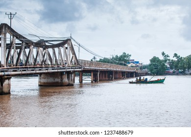 Kampot, Cambodia - SEPTEMBER 22, 2013: Landscape orientation view, couple fisherman with old fishing boat pass under the old French bridge over the Praek Tuek Chhu River. Kampot Province.