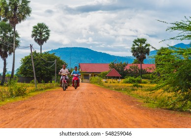 KAMPOT - DECEMBER 14: Cambodia rural scenery with two men who hold fishing rods drive scooters on terracotta dirt road with palmyra palm trees (palm fruit) on December 14, 2016 in Kampot, Cambodia
