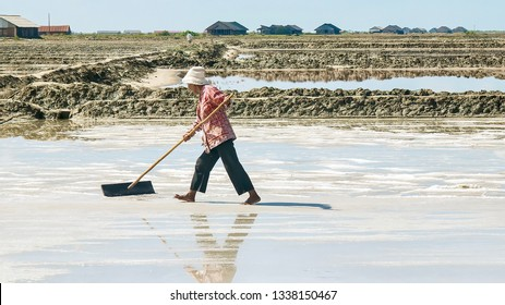 Kampot Province, Cambodia - March 6, 2012. Showing sea salt production. A female Cambodian worker harvests sea salt from one of several fields on a farm which produces salt from evaporating seawater.