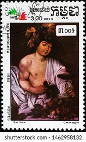 """KAMPUCHEA - CIRCA 1985: A stamp printed in Kampuchea (Cambodia) shows a painting """"Bacchus"""" by Caravaggio with the same inscription, from series """"Italian painting"""", circa 1985"""