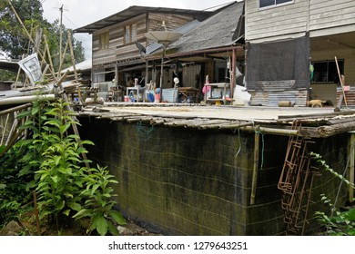 KAMPUNG ANNAH RAIS, SARAWAK, MALAYSIA — APRIL 18, 2018. Doors of multiple family homes open onto a communal area of this longhouse of the Bidayuh tribe on the island of Borneo.