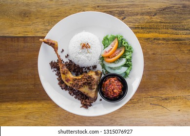 kampung fried chicken or ayam goreng kampung with sambal and lalapan on white plate