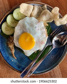 Kampung fried rice served with salted fish, egg, fish crackers and slices of cucumber, closeup view with details.