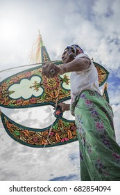 Kampung Mek Mas, Kota Bahru, Kelantan / Malaysia - July 15, 2017 : A low angle shot of an elder waiting for the right moment to fly his uniquely design kite.