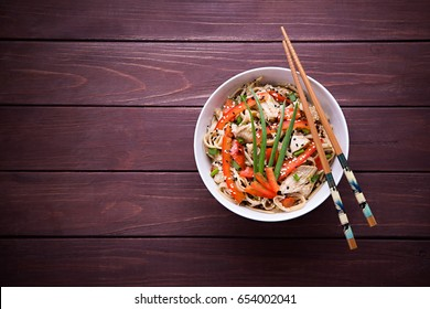 Kamut noodles in Asian style with chicken in bowl on dark wood background with place for text