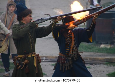 Kamyanets-Podilsky, Ukraine, 10/01/2016. The musketeers and cossacks shooting with muskets. The rifle with fire and sparks. Reenactment of the 17th century battle. Attack of cossacks. Living hirtory.