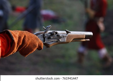 KAMYANETS-PODILSKY, UKRAINE - OCTOBER 3, 2009: Members of history club wear historical uniform 17 century during historical reenactment. The mans hand with flintlock muzzle-loading pistol.