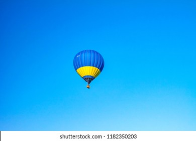 Kamyanets-Podilskyi, Ukraine - May 2017: Colorful hot air balloon in flight over blue sky.