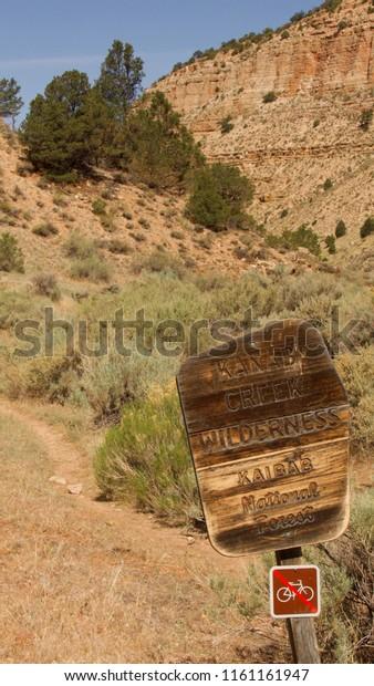Kanab Creek Wilderness, Arizona, USA, June 2018.  A wooden sign marks the Kanab Creek Wilderness with a hiking trail in the background.