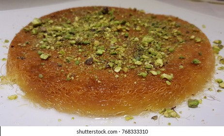Kanafeh arabic desserr with almonds on a white plate