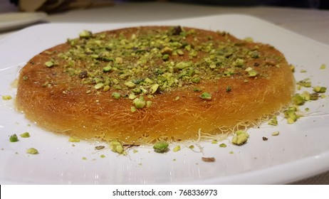 Kanafeh arabic dessert with green almonds on a white plate