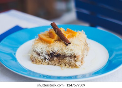 Kanafeh, baklava dessert with apples, cinnamon and cranberry in white blue plate