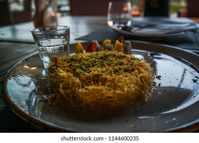 Kanafeh is a traditional Arabic dessert made with thin shredded pastry soaked in sweet, sugar-based syrup, and typically layered with cheese, or with other ingredients such as clotted cream or nuts