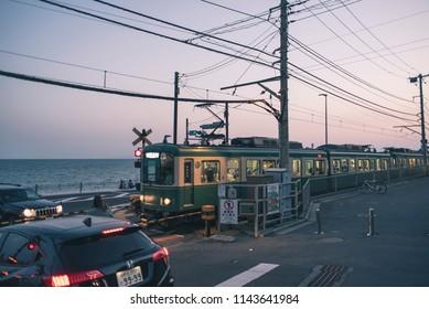 Kanagawa, Japan - June 2, 2018: View of train passing on railway crossing near Kamakura high school (Kamakura Kokomae) station at sunset. Famous because comic series Slam Dunk took place here.