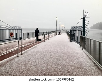 Kanagawa, Japan - March 23, 2019: View of mans clearing the snow at the port of the pirate ship at Hakone lake Ashi when the snow is started falling down in Kanagawa, Japan.