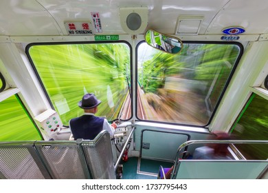 KANAGAWA, JAPAN -MAY 21, 2014: Driver drive the Oyama Cable Car descending from Mount Oyama. The Oyama Cable Line is a Japanese funicular line in Isehara, Kanagawa. (Blur with long exposure shot)