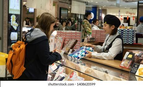 KANAGAWA PREFECTURE, YOKOHAMA, JAPAN - MAY 01 2019: An omiyage (Japanese souvenir) goods shop clerk presenting a consumable product to a customer at Yokohama Sogo Seibu department store.