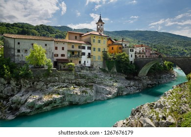 Kanal, Slovenia - May 19, 2017: Colorful stucco houses on the turquoise Soca River with stone bridge at old section of Kanal Slovenia with Assumption of Mary church